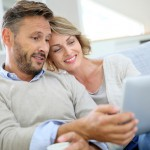Middle-aged couple relaxing in sofa and using tablet